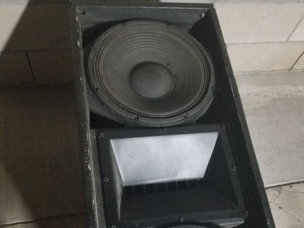 The damaged speaker needs to be unscrewed from the cabinet. Then once it is unscrewed, left it up carefully but not too high as it is connected to the amp. Carefully disconnected the cables from the speaker and place the speaker on top of a table.