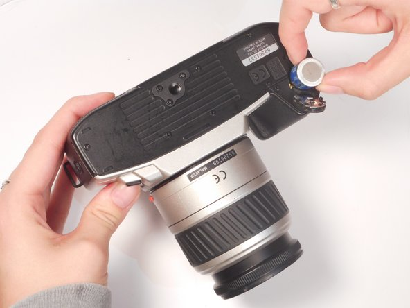 Image 1/1: Remove the two batteries from the battery chamber by picking them up.