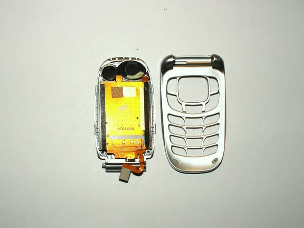 Image 3/3: Next slide the connector cable out of the slot on the back side of the phone and the screen will be disconnected from the key pad body.