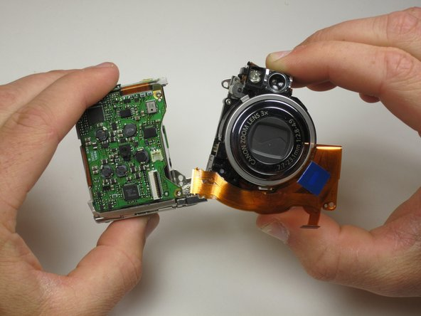 Finally, pull the lens assembly away from the camera frame. Make sure that none of the ribbon cables are tangled up.