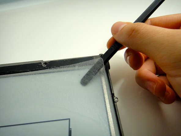 Image 2/2: The plastic screen is held on by a thick layer of glue. Be patient when lifting the screen to avoid bending or breaking the thin plastic.