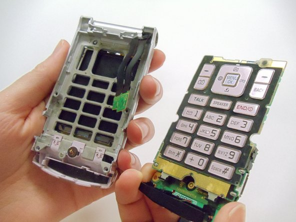 Image 3/3: Once the keys are free from the casing, close the phone and pull the motherboard from the back of the phone the remainder of the way with your fingers.
