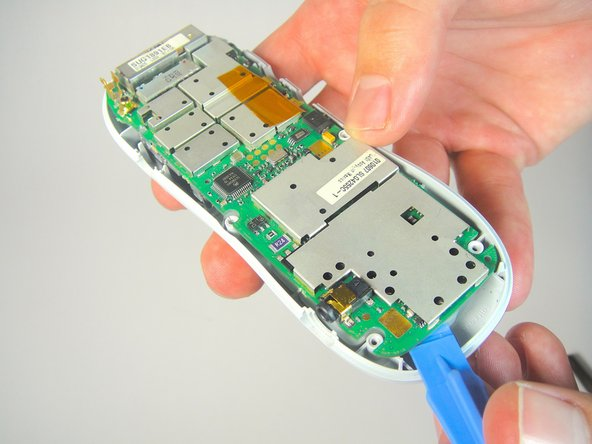 Place your plastic opening tool in between the motherboard and the front cover of the phone