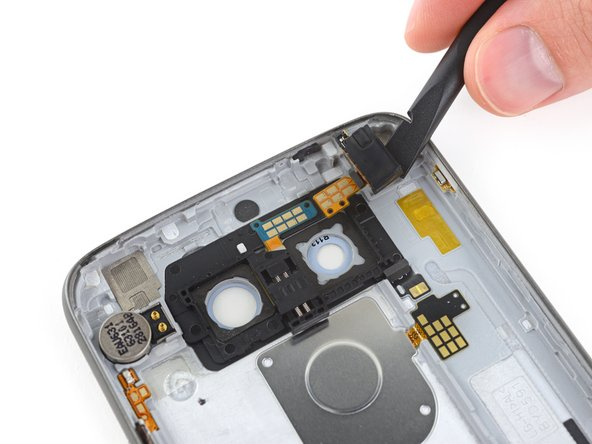 Image 1/3: A hefty and ''very'' well-adhered metal plate keeps the back button pressed to the case, and probably adds ingress proofing. (It also reminds us a bit of the [https://www.ifixit.com/Teardown/iPhone+SE+Teardown/60902#s127231|bi-metal Apple logo|new_window=true].)
