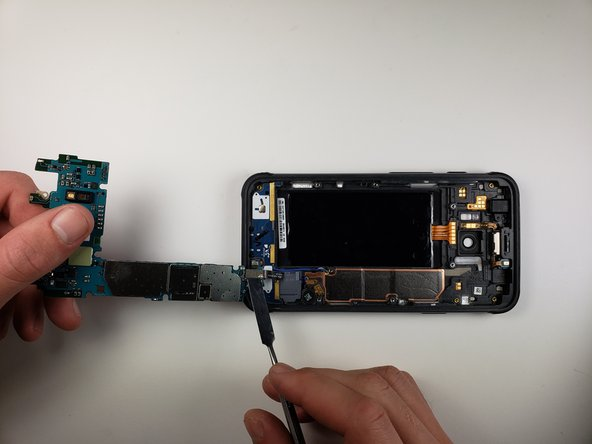 Use your hands and a metal spudger to lift the motherboard out of the phone.