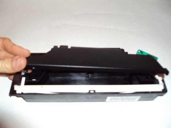 Remove the black face plate from the scanner head. Push on the two black tabs located on opposite sides of the scanner head. One of them is located in the groove the control panel normally rests in.