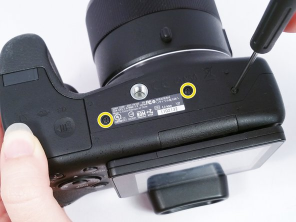 Remove the 2 (4 cm) Phillips head screws on the right side of the camera.