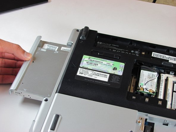 Image 2/3: Pull the optical drive completely out of the computer frame.