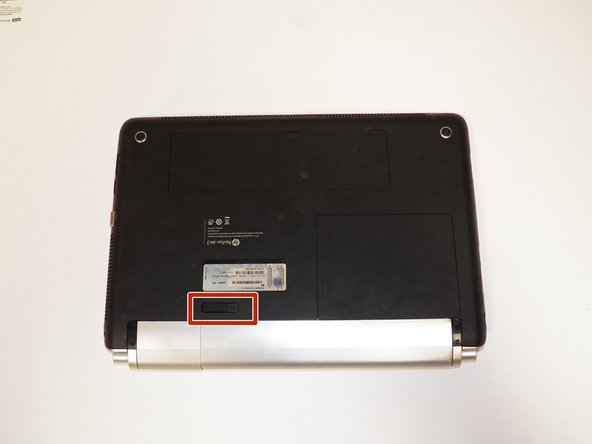 Place the laptop upside down on a stable surface and locate the battery ejection switch.
