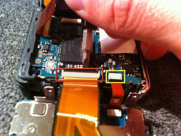 Using a flat head screw driver gently pry up the tab securing the ribbon cable from the display screen to the camera sensor and battery housing.