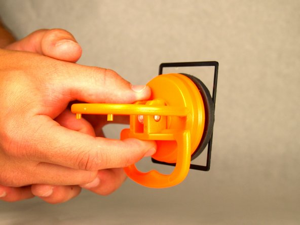 Release the broken screen by pulling down the lever of the suction cup.