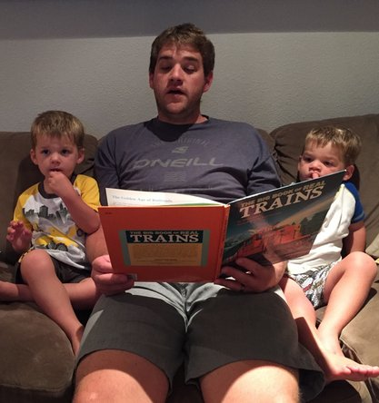 Father reading a book about trains to his sons