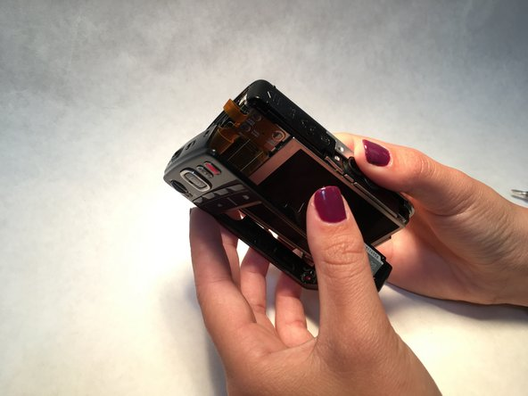 Starting at the top of the camera, remove the front and back of the camera with the prying tool