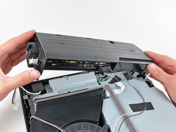 Image 1/2: Remove the power supply from the PS3, minding any cables that may get caught.