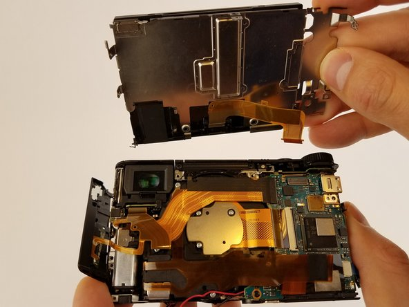Image 2/2: Remove the ribbon cable connecting LCD display to camera sensor and battery housing gently.
