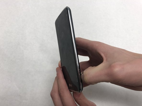 Insert a fingernail into the notch on the bottom right corner of the phone.