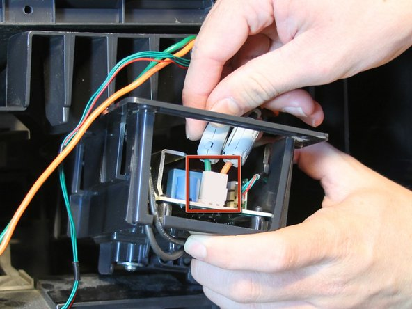 Disconnect the orange and green power connection from the lamp ballast by holding the white tab on the connector and pulling straight out.