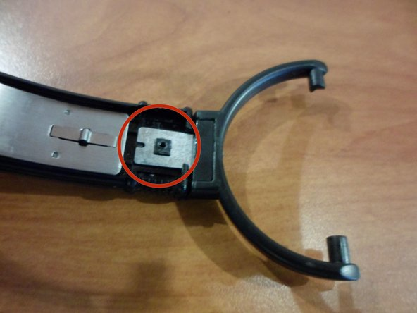 Turn the headphones so that the inner tab of the speaker clamp where it attaches to the headband can be seen.