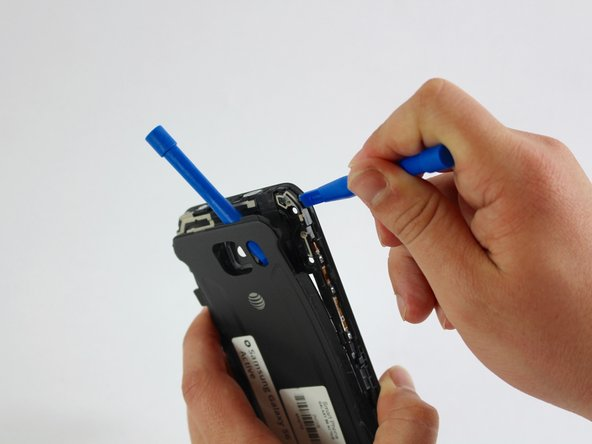 Insert a plastic tool to pry open the black and beige piece covering the volume button connection.