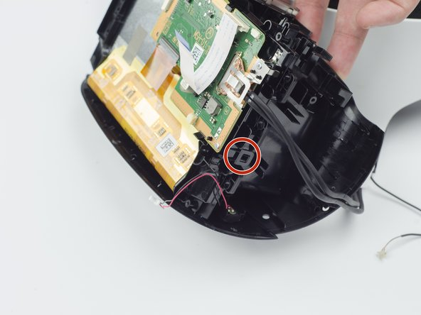 Using your fingers, lift up on the sides of the black plastic piece holding the circuit board in place.