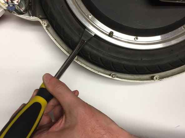 Insert the spoon tire iron in between the metal rim and rubber tire.