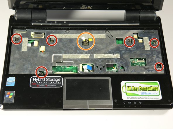 Image 2/2: Having already removed the keyboard, locate the six  7mm screws on the silver plate in the keyboard housing.