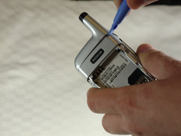 Use a plastic opening tool to remove the silver cover over the antenna.