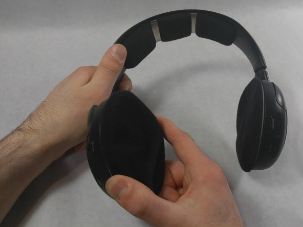 Grip the ear pad with one hand and steady the headset on the other.