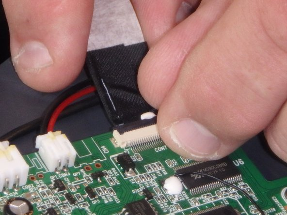 Disconnect the ribbon cable by flipping up the latch on the connector and then pull the ribbon out.