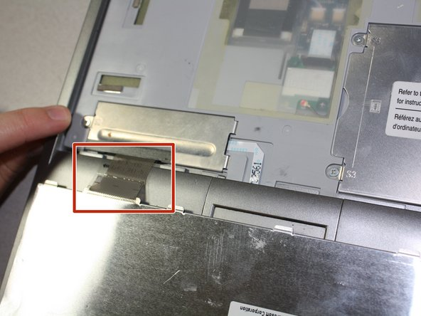Find the white ribbon connector (where the keyboard is still attached to the rest of the laptop).