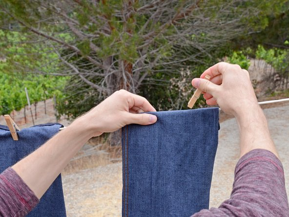 Image 1/3: Allow your pants to dry completely before removing the clothespins and taking them down.