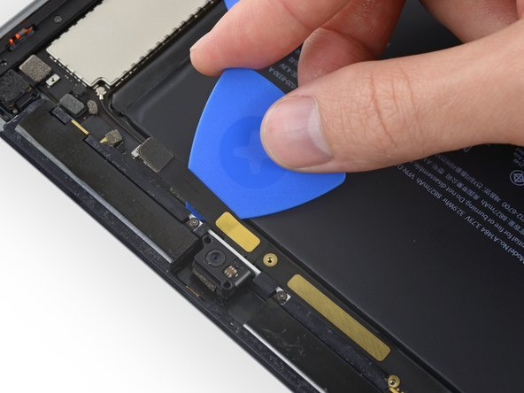 Slide an opening pick underneath the front-facing camera cable to break up the adhesive holding it in place.