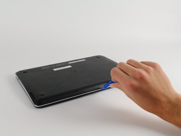 Use the plastic opening tool to gently work around the edge of the Chromebook until the back panel starts to lift off.