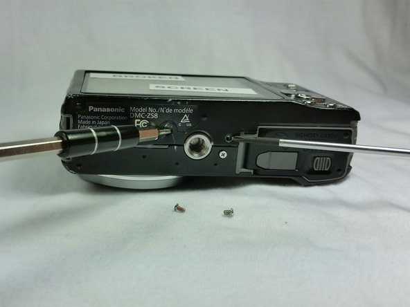 Replace the front panel and install the screws on the bottom side of the camera.