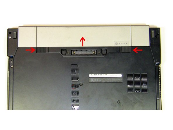 Simultaneously slide the battery latches (outlined by the red box) to the dock connector in the middle.