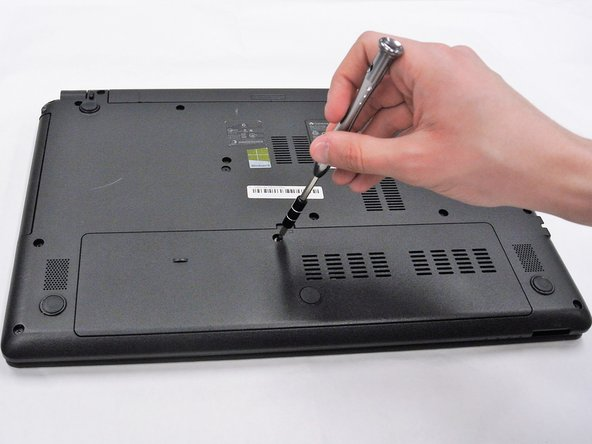 Use a PH0 Phillips head screwdriver to remove the 9.0 mm screw on the rectangular panel underneath the device.