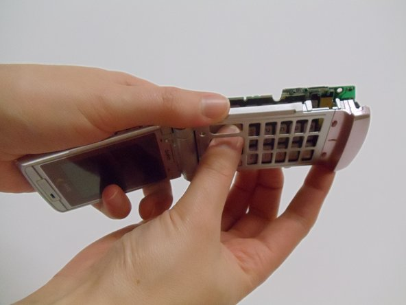 Image 1/3: Once the keys are free from the casing, close the phone and pull the motherboard from the back of the phone the remainder of the way with your fingers.