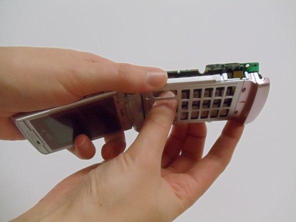 Ouvrez le téléphone et tenez fermement le boîtier du téléphone d'une main et poussez la carte mère hors de l'étui avec l'autre en appuyant sur les touches.