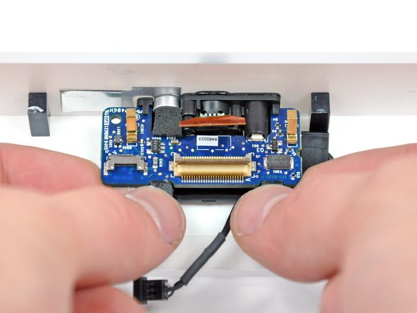 Use your thumbs to simultaneously rotate both retaining tabs away from the camera board while pushing the board up from either side with your index fingers.