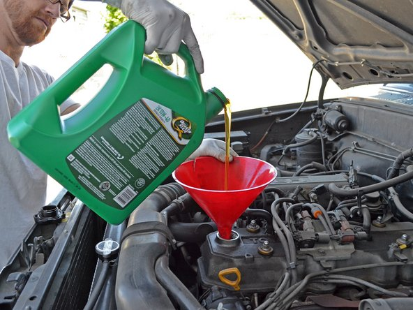 Pour 4.5 quarts of 10W-40 oil into the engine. Use one hand to stabilize the funnel to help prevent spills.