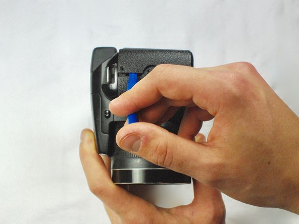 Use a plastic opening tool to separate the back panel from the camera on the left side.