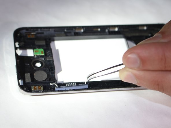 Using a pair of tweezers, remove the volume button by unlatching the two white bands holding it in place.
