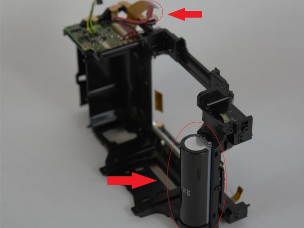 The flash capacitor will be to the right of the lens on the front of the camera.