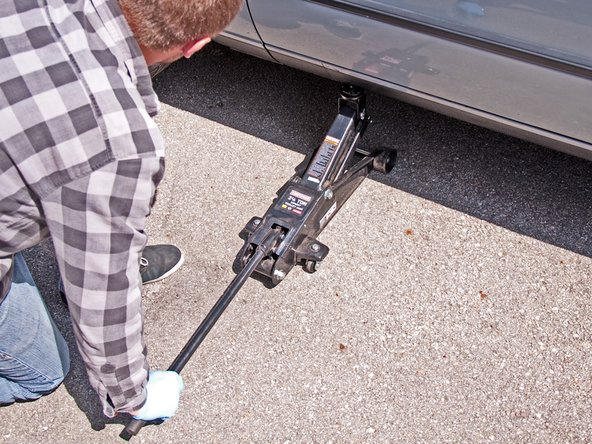 Use a hydraulic jack (or your factory jack) to lift the driver's side of the car.