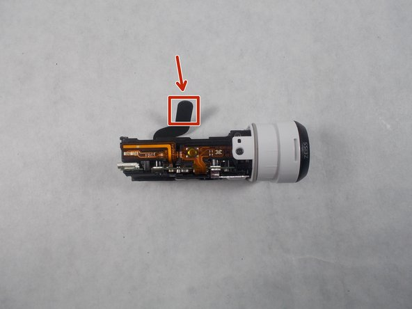 Image 2/3: Pull the tabs on the bottom and top of the lens, and pull outward, this will remove the lens housing from the body.