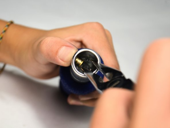 Reach in carefully with the small needle-nose pliers and firmly grab the golden fastening button.