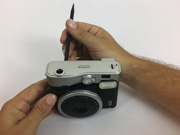 Use the black spudger to pry off the silver casing on the top and the bottom of the camera.