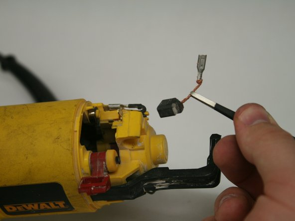 Use tweezers to gently remove the brush and cable.