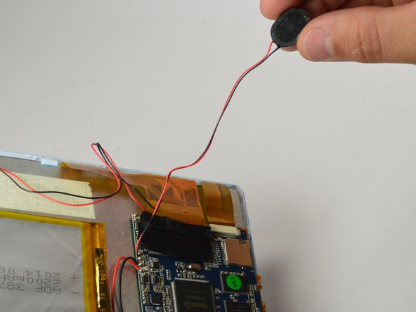 Remove two strips of tape: One holding down the wires and the other holding down the internal speaker.