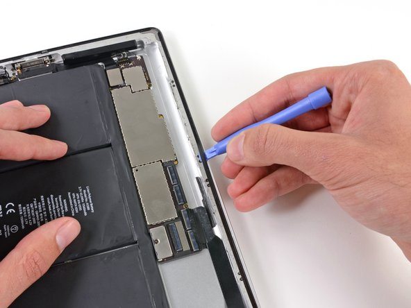 In the same manner, continue sliding the plastic opening tool along all the left edge of the iPad.